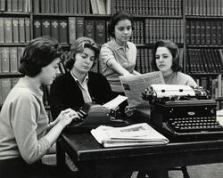 Students in library with typewriters, newspapers
