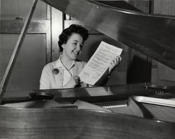 Student Barbara Gross (composer of SCW alma mater) seated at piano