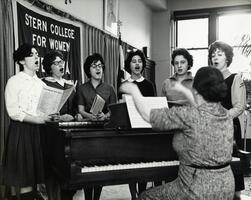 Students singing at piano with instructor