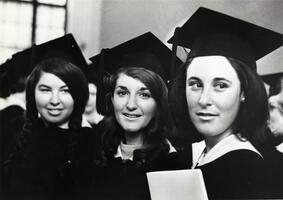 Three graduates in caps, gowns at Commencement