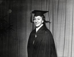 Member of first graduating class Marilyn Bell in cap, gown