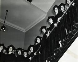Students of first graduating class on stairs in caps and gowns