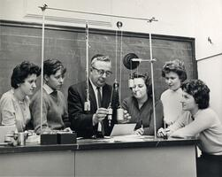 Students with Physics Professor Henry Lisman demonstrating with weights