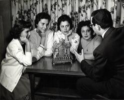 Students at table with menorah listening to a talk