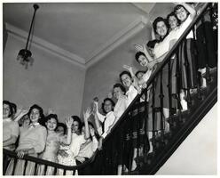 Students of first entering class waving on stairs