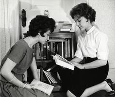 Two students examining books