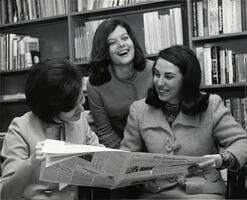 Three students in library reading Yeshiva College student newspaper The Commentator