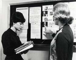 Students reading item on bulletin board